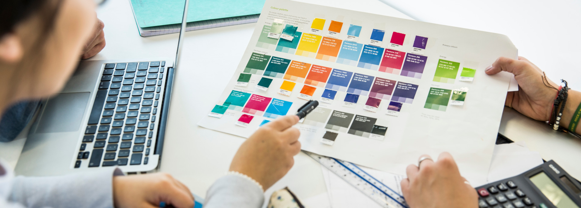 Two people looking at printed colour swatches