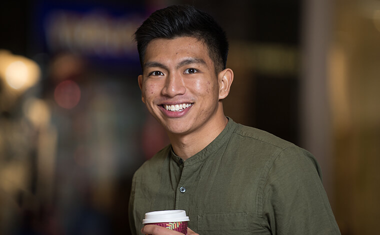 A student holding a coffee and smiling