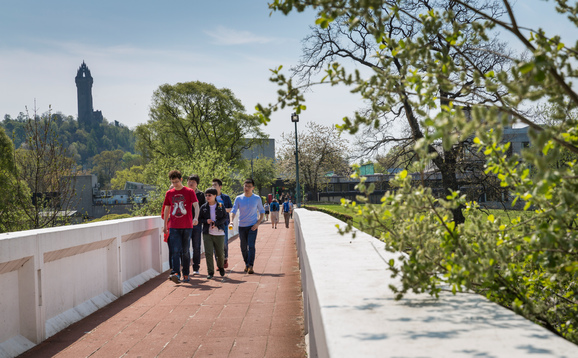 Students walking over the loch on campus