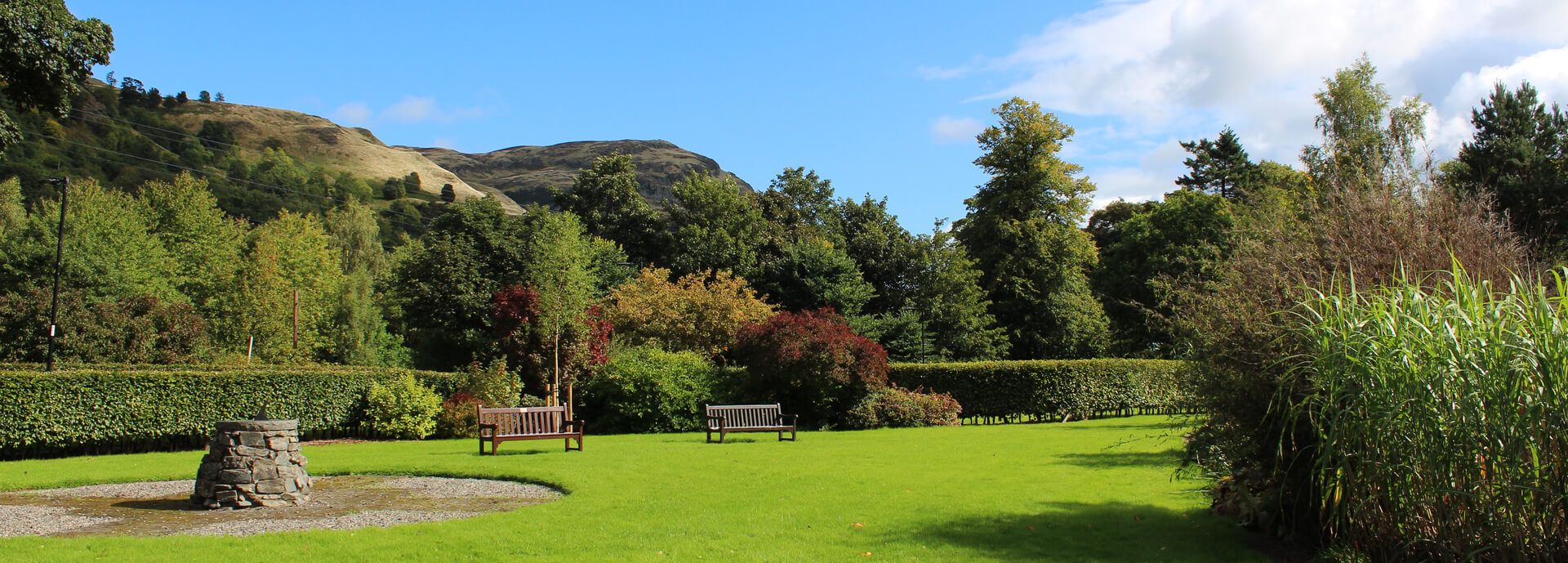 Garden, benches, hill, sun dial under a blue sky