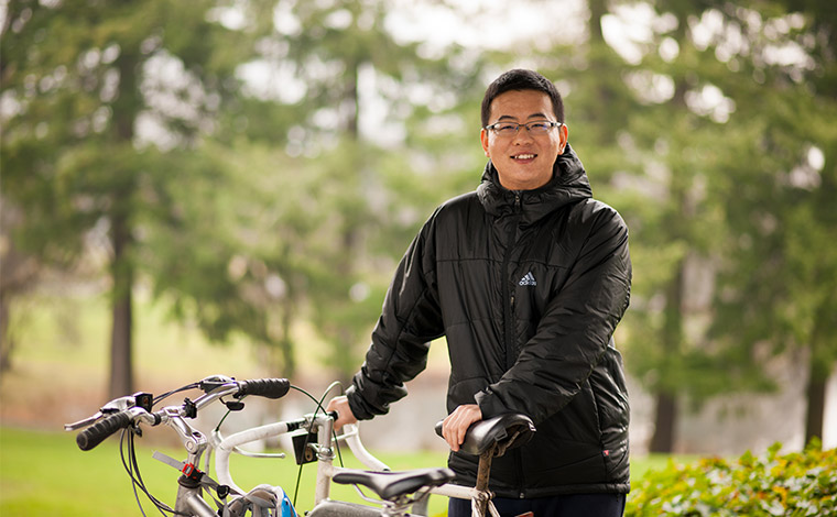 Chinese student with bicycle on campus