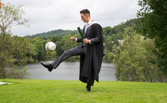 Student at graduation with football