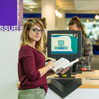 student in library at self service machine