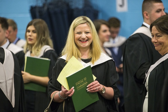 Graduate in ceremony holding graduation programme