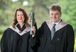 a man and woman standing together smiling both holding a degree