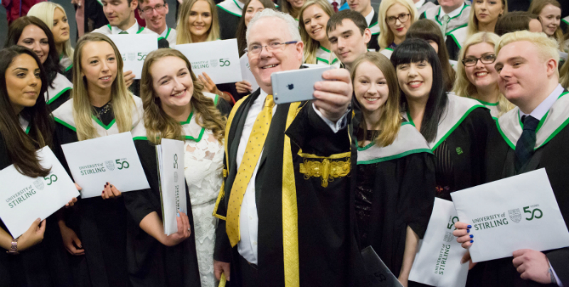 recent graduates with smiles on their faces taking a selfie with stirlings principal