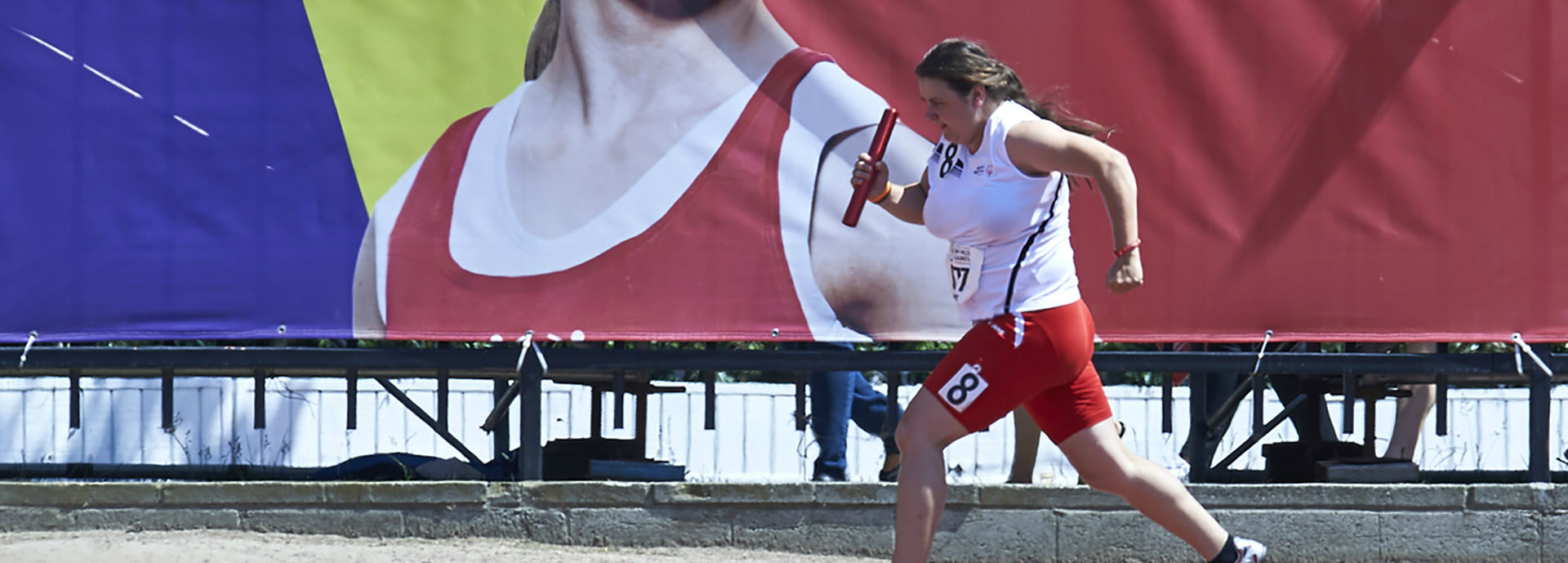 Special Olympics female athlete running with relay baton