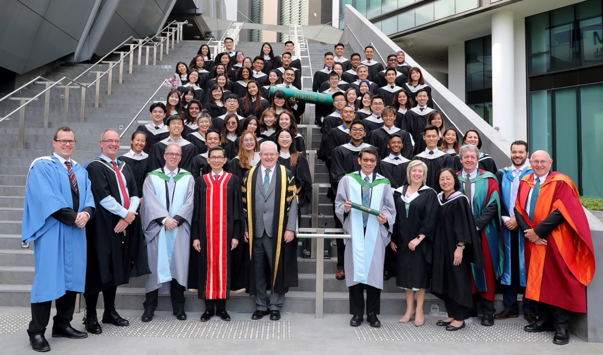 Senior staff and students in graduation robes standing on stairs