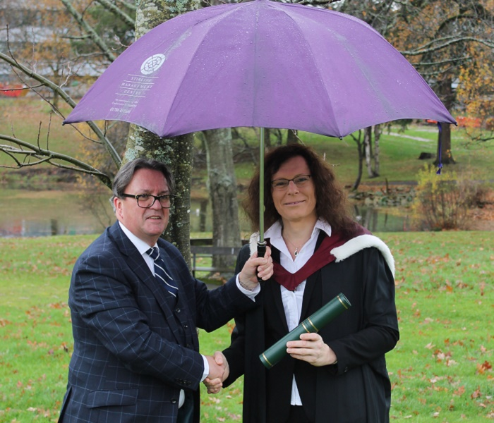 man in suit and woman in graduation robes under an umbrella