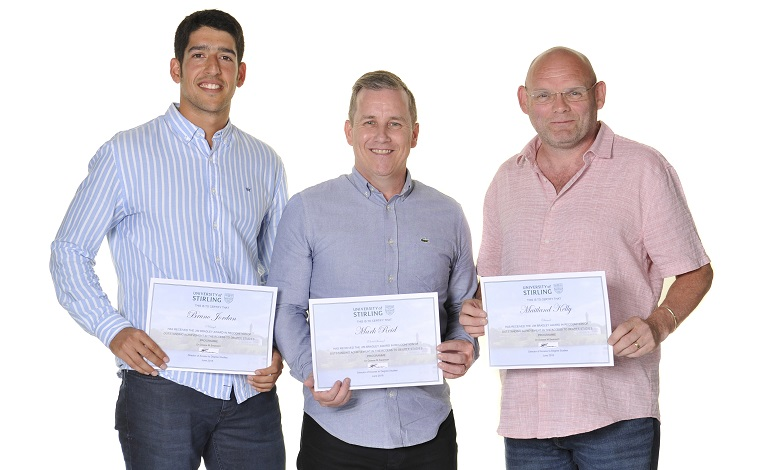 Group of three men with certificates