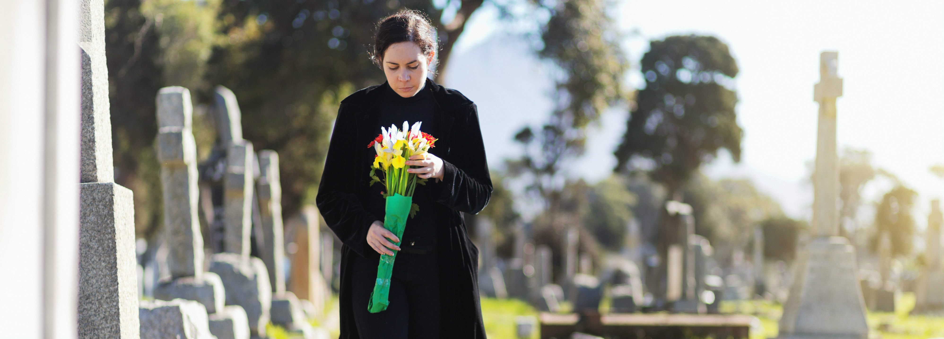 Woman wlaking through graveyard holding flowers