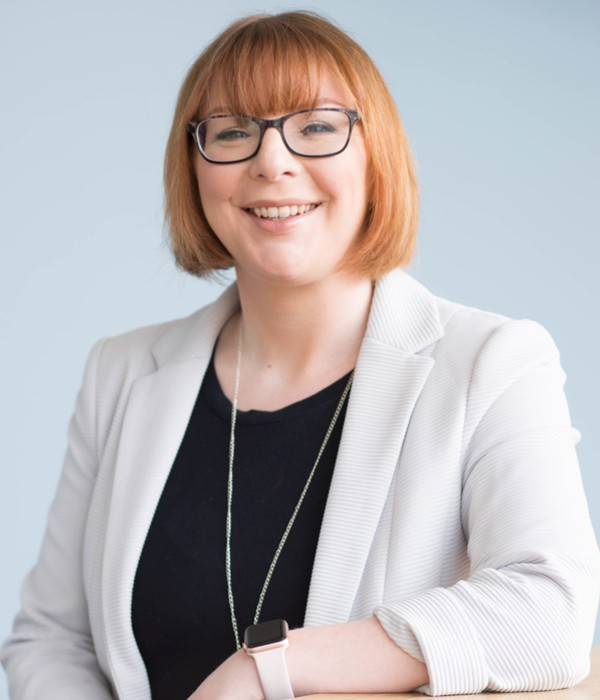 Dr Vikki McCall. Female with red bobbed hair cut, black glasses look straight to camera and wearing a white blazer and black top