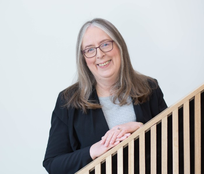 Prof Alison Bowes has shoulder length grey hair and wears dark, square glasses. She is looking to the camera smiling with her hands clasped leaning on the bannister of the staircase she is standing on