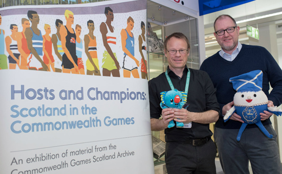 Research staff beside Commonwealth Games banner