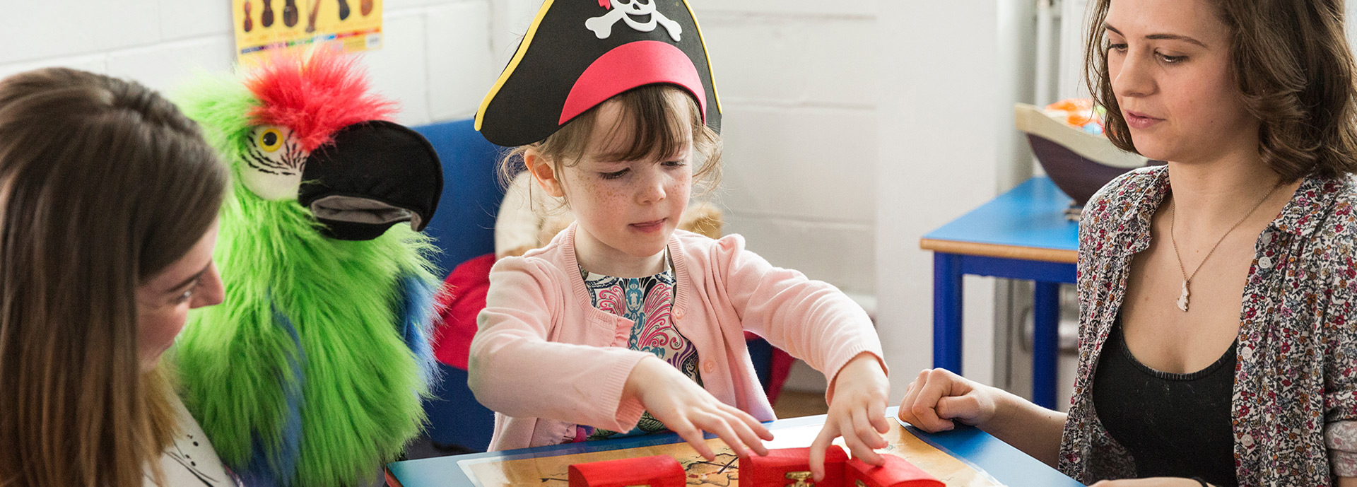 Two researchers, one with toy parrot, and child with pirate hat run an experiment