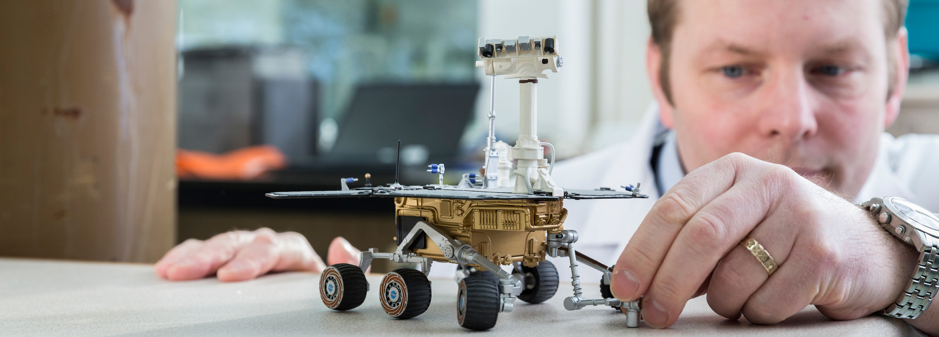 Man with model of Mars rover