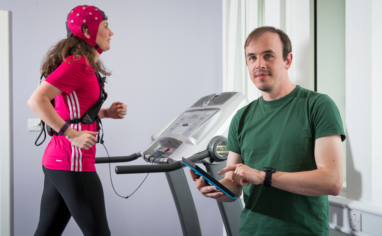 Man with clipboard and woman on running machine