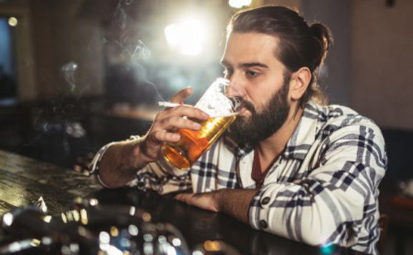 man drinking beer and smoking